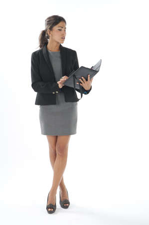 Serious portrait of self confident female young business executive, looking at her notebook. photo