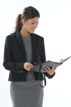 account executives: Female young business executive looking up in her notebook.