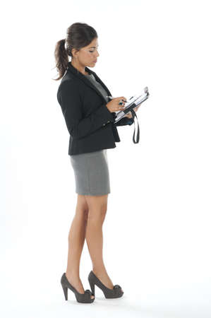 Full length profile of female young business executive writting on her notebook.