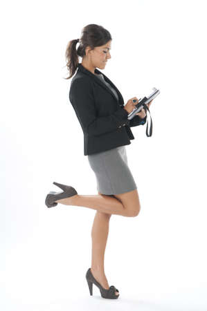 Full length profile of satisfied female young business executive writting on her notebook. Stock Photo - 14429471