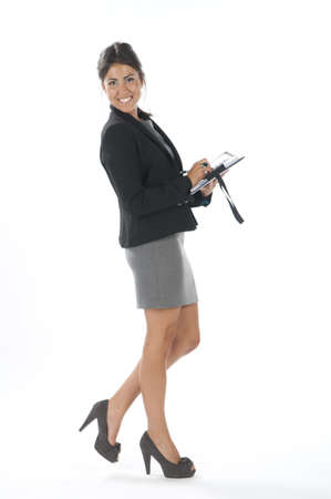 Full length profile of happy female young business executive writting on her notebook. Stock Photo - 14429468