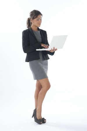 Self confident female young business executive looking at her laptop.