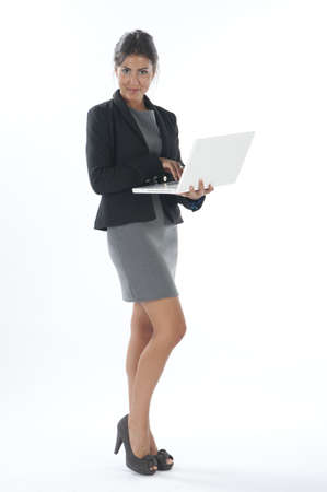 Self confident female young business executive holding laptop looking at camera.