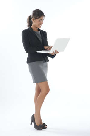 Happy female young business executive writing on her laptop.