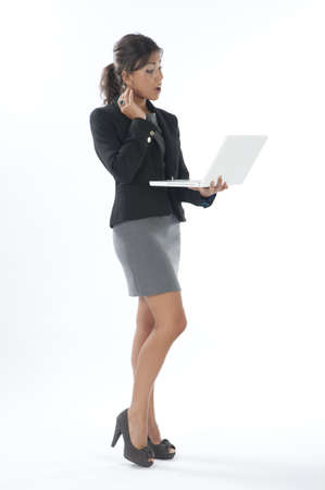 Surprised female young business executive looking at her laptop. Stock Photo - 14429497
