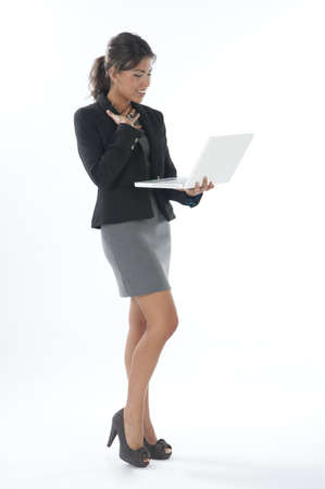 Surprised female young business executive looking at her laptop. Stock Photo - 14429509