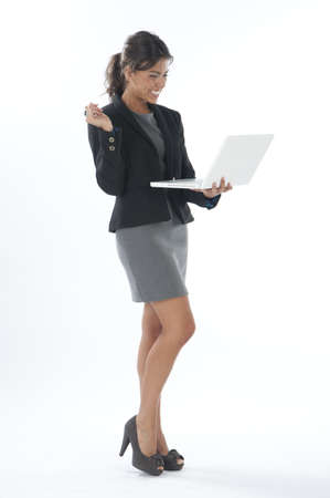 Happy female young business executive looking at her laptop. photo