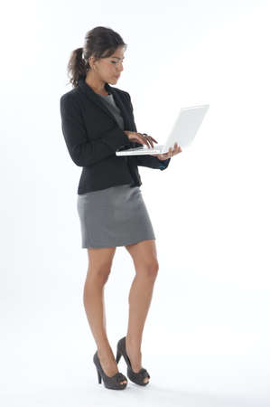 Self confident female young business executive writing on her laptop.
