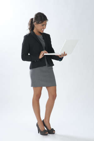 Happy female young business executive looking at her laptop.