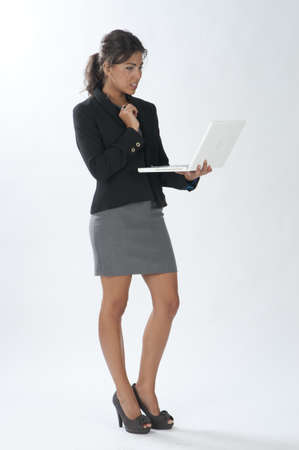 spaniard: Serious female young business executive looking at her laptop. Stock Photo