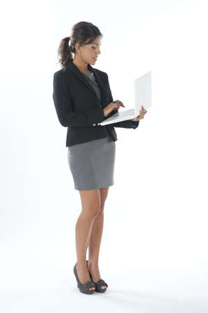 Female young business executive typing on her laptop. Stock Photo - 14429491