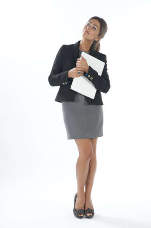 Self confident female young business executive looking away holding laptop. Stock Photo