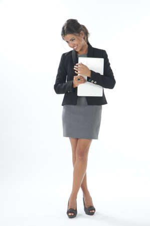 Self confident female young business executive looking down, holding laptop. photo