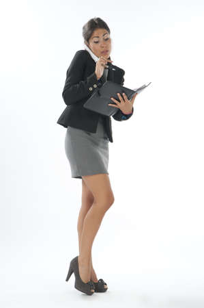 Bussy young executive female, talking on the phone and writing on her notebook. Stock Photo - 14429666