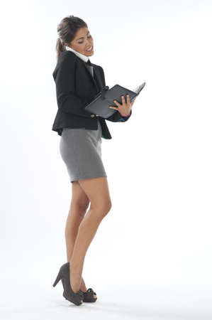 Bussy young executive female, talking on the phone and writing on her notebook. Stock Photo