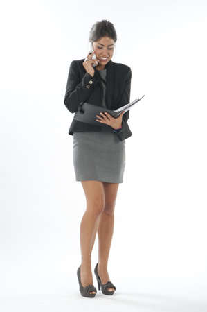 account executives: Bussy young executive female, talking on the phone and writing on her notebook. Stock Photo
