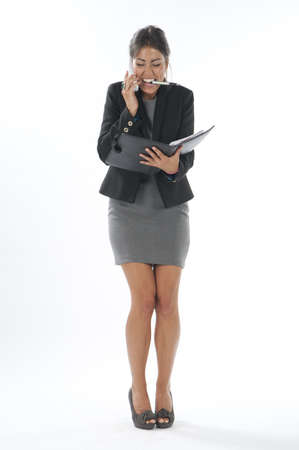 account executive: Bussy young executive female, talking on the phone and writing on her notebook. Stock Photo