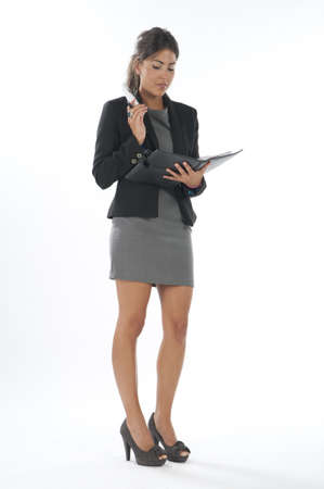 Bussy young executive female, talking on the phone holding notebook. photo
