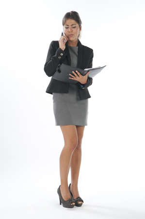 Bussy young executive female, talking on the phone holding notebook. Stock Photo - 14429693