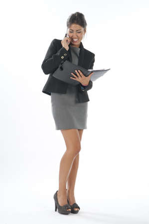 office wear: Bussy young executive female, talking on the phone holding notebook.