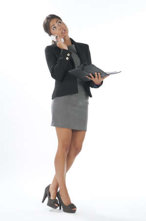 Serious young executive female, talking on the phone holding notebook. Stock Photo - 14429641