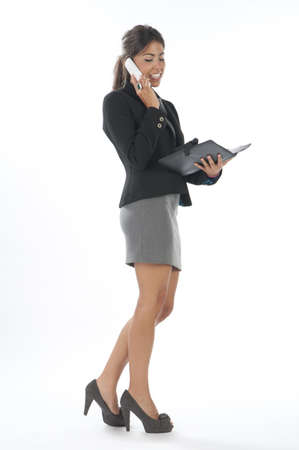 Smiling young executive female, talking on the phone holding notebook. Stock Photo