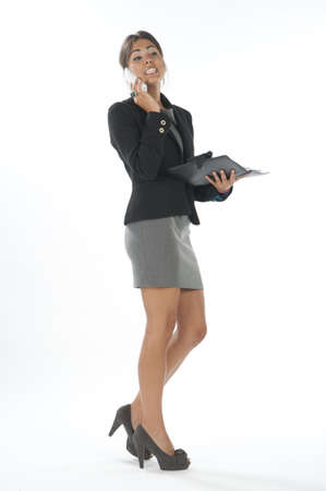 Bussy young executive female, talking on the phone holding notebook.