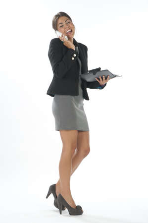 Young business executive female laughing on the phone holding notebook.