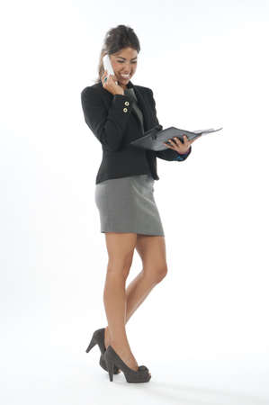 account executive: Young executive female, smiling while talking on the phone holding notebook. Stock Photo