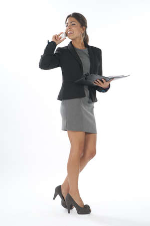 smiing: Young business executive female, smiing while talking on the phone holding notebook.