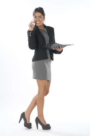 Young business executive female, smiling while talking on the phone holding notebook.