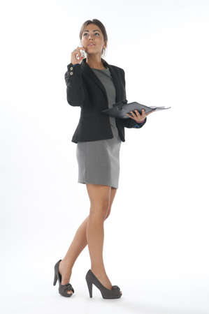 Young business executive female day dreaming while talking on the phone holding notebook. Stock Photo - 14429591