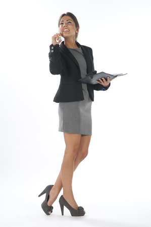 Young business executive female, day dreaming while talking on the phone, holding notebook.