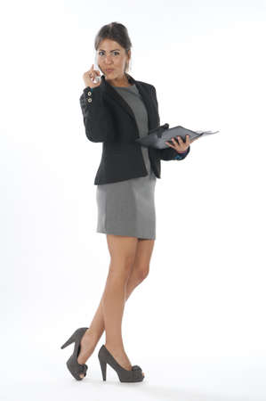 Young business executive female, on white, talking on the phone, looking at camera.