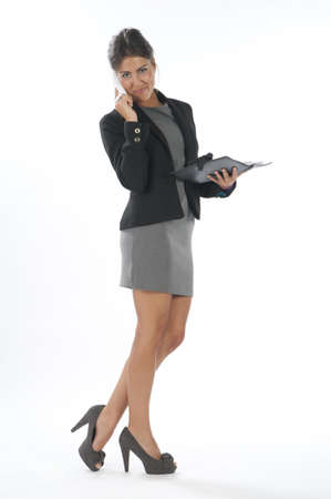 account executive: Young business executive female, on white, talking on the phone, looking at camera.