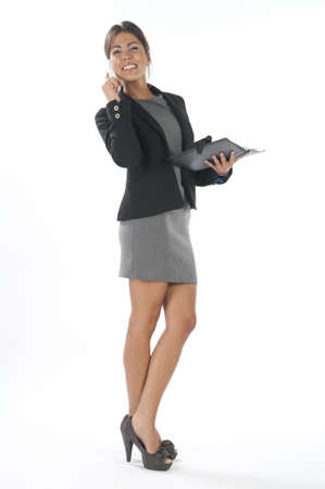 Young business executive female, on white, talking on the phone, looking away. Stock Photo