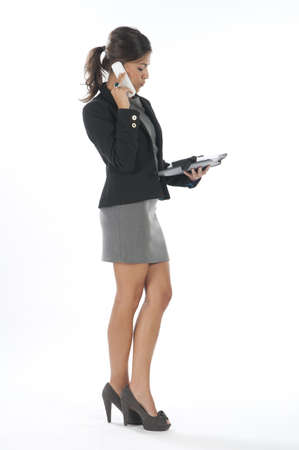 Young business executive female, on white, talking on the phone, looking down.