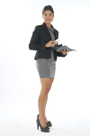 Young business executive female, on white, holding phone, looking at camera. Stock Photo