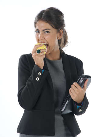 Waist up, young business executive woman, on white, biting an apple. photo