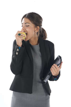 Waist up, young business executive woman, on white, biting an apple. Stock Photo - 14429856