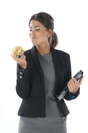 Waist up, young business executive woman, on white, biting an apple. Stock Photo - 14429853