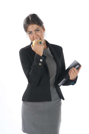 Waist up, young business executive woman, on white, biting an apple. Stock Photo - 14429838