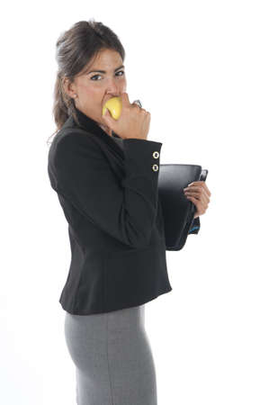 Waist up, young business executive woman, on white, biting an apple.