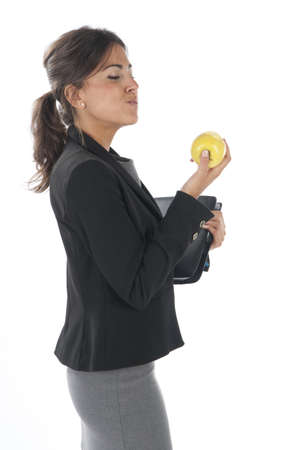 Waist up, healthy young business executive woman, on white, eating an apple. photo