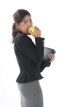 Waist up, healthy young business executive woman, on white, eating an apple. Stock Photo - 14429760