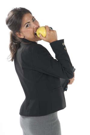 attractiveness: Medida de la cintura para arriba, sana empresa joven mujer ejecutiva, en blanco, comiendo una manzana.