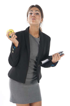Waist up, healthy young business executive woman, on white, eating an apple. Stock Photo - 14429870