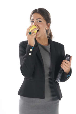 Waist up, healthy young business executive woman, on white, eating an apple. Stock Photo - 14429857