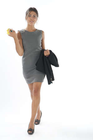 Full length healthy young business executive woman, on white, walking holding an apple.