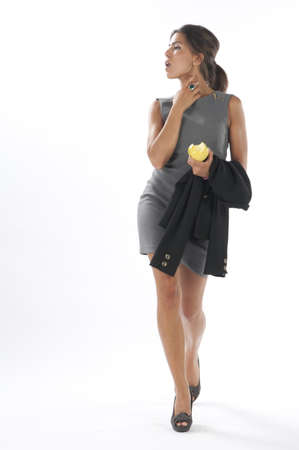 Full length healthy young business executive woman, on white, looking away, walking holding an apple.